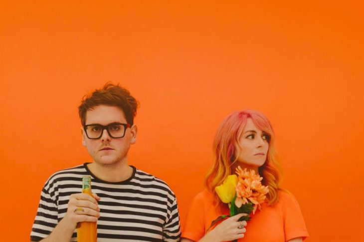 Two members of Repeat Repeat in front of orange backdrop