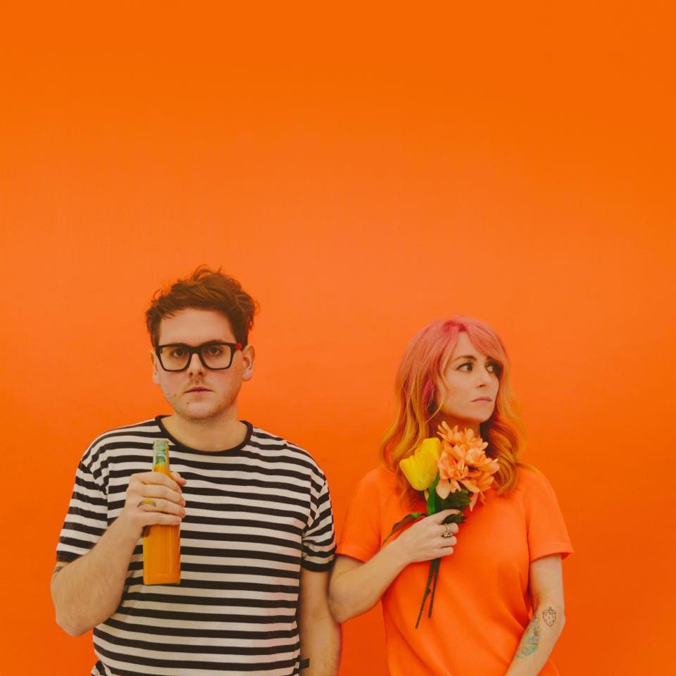 Repeat Repeat duo in front of orange backdrop.
