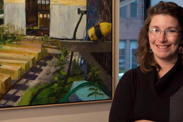 Kathi Smith standing in front of one of her paintings