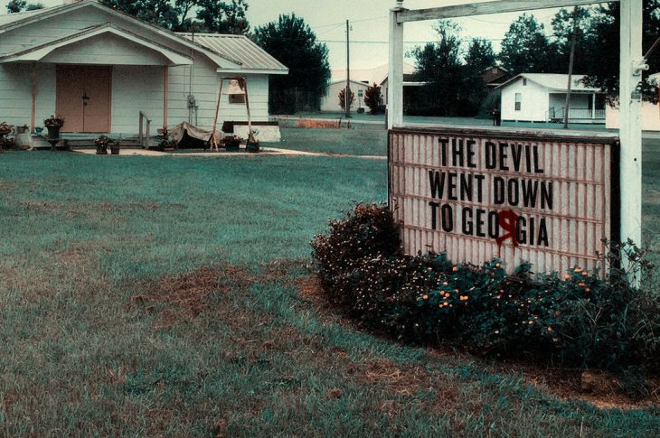Devil Went Down To Georgia artwork. Signboard in front of church with song title.