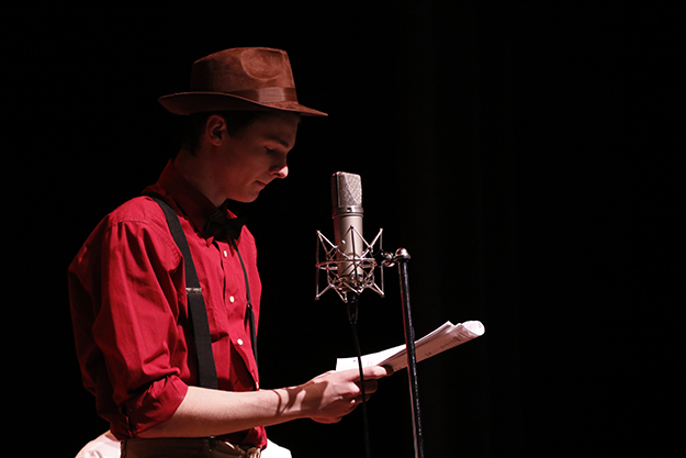 Photo of cast member (man in red shirt and brown hat) standing before a microphone.