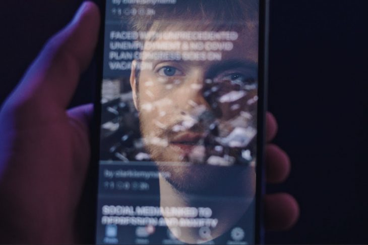 Artist's face reflected in a phone screen.
