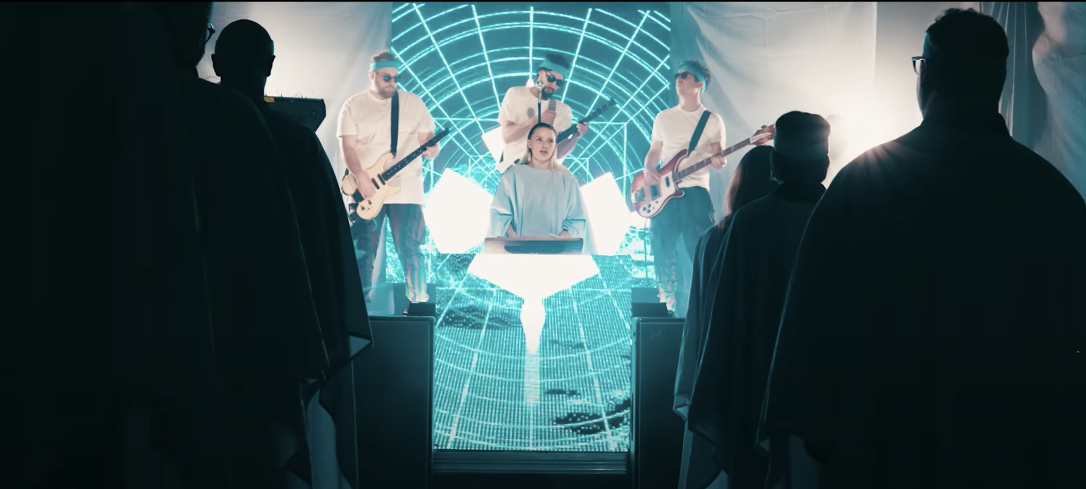 image from Dominic Lavoie music video. dark audience in church with band behind blonde woman draped in blue robes.