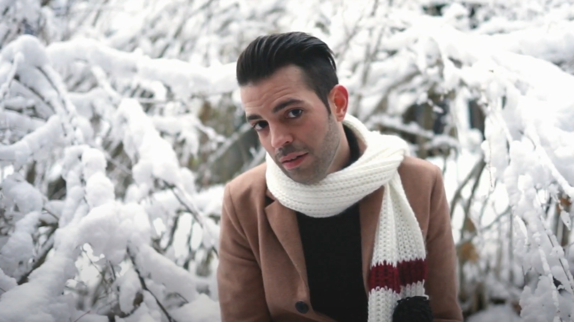 Dean Ford in jacket and scarf standing in front of snow covered trees