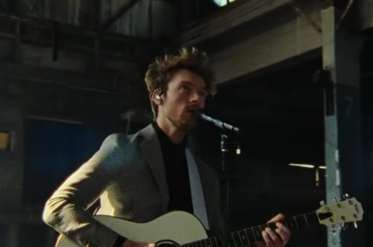 FINNEAS wearing a suit playing an acoustic guitar