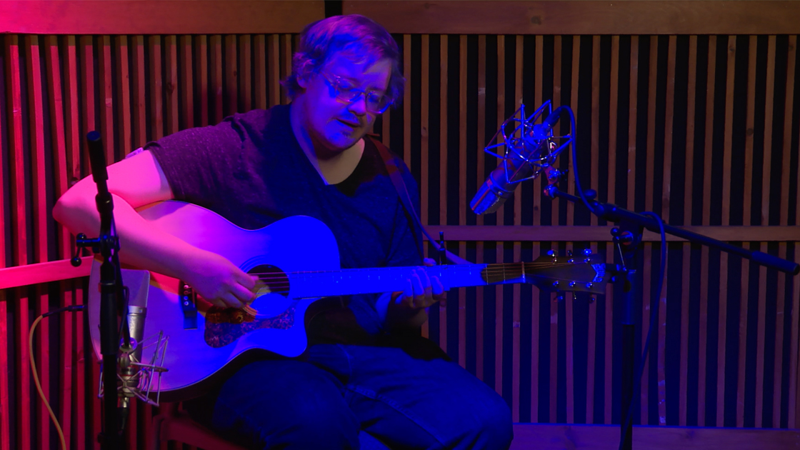 Dustin Saucier performing with acoustic guitar