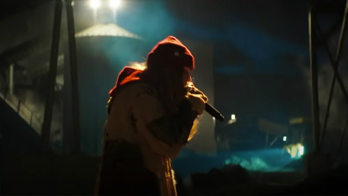 still image from Girl In Red singing in a warehouse.