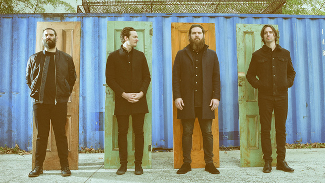 press photo of Manchester Orchestra members each standing in front of a colorful door.