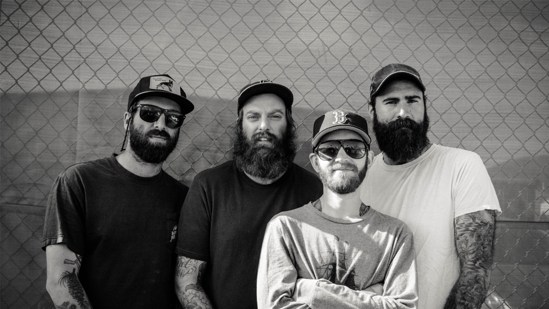 Black & white photo of members of Four Year Strong in front of chain link fence.