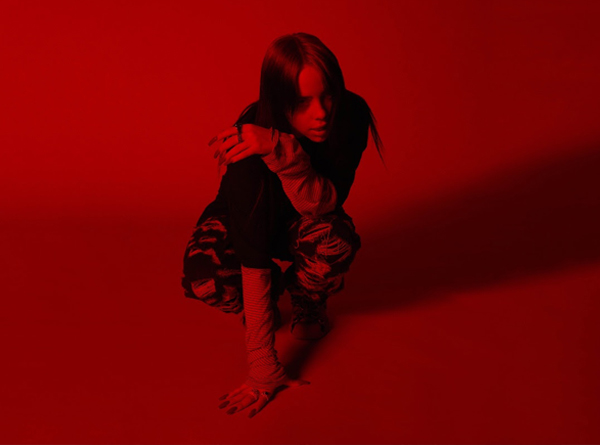 Billie Eilish photographed in red light.