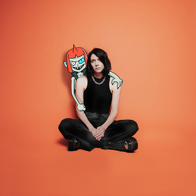 K. Flay's Inside Voices EP album artwork. artist sitting in front of orange backdrop with cartoon figure leaning over her.