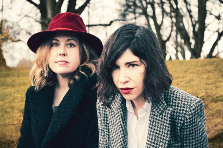 Photo of Sleater Kinney's Corrin Tucker & Carrie Brownstein outside in front of trees.